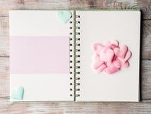 Coeurs en pastel roses et reliure à anneaux pourpre de carte vierge Images stock