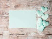 Coeurs en pastel verts et carte de papier d'invitation Photo stock