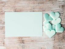 Coeurs en pastel verts et carte de papier d'invitation Photos libres de droits