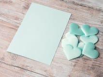 Coeurs en pastel verts et carte de papier d'invitation Photographie stock
