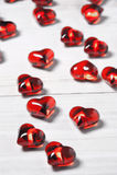 Coeurs en plastique d'effet en verre clair sur une table en bois blanche Images stock
