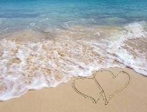 Coeurs en sable de bord de la mer avec le ressac d'océan Photo libre de droits