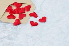 Coeurs en soie rouges dans l'enveloppe postale ouverte Photographie stock libre de droits