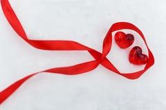 Coeurs en verre rouges brillants avec le ruban sur la neige Photos libres de droits