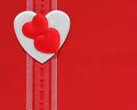 Coeurs et bande sur un fond rouge Photo stock