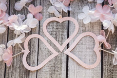Coeurs et fleurs roses et blancs sur une table en bois Images stock