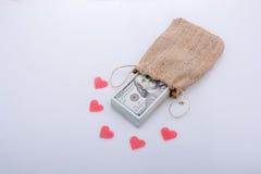 Coeurs et paquet rouges de dollarin des USA un sac Image libre de droits