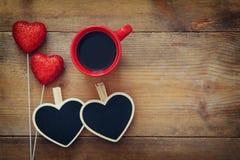 Coeurs et tasse de café rouges sur le fond en bois Image libre de droits