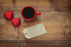 Coeurs et tasse de café rouges sur le fond en bois Photo stock