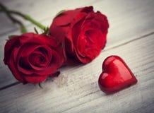Coeurs et un bouquet des roses rouges sur le conseil en bois Photo libre de droits