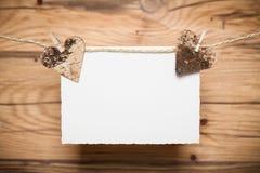 Coeurs et une carte vierge de message sur une ligne Photographie stock libre de droits