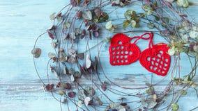 Coeurs faits main rouges d'amour de crochet sur le fond en bois bleu de texture Concept de carte de jour de valentines Coeur pour Images stock