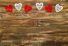Coeurs floraux accrochant au-dessus du fond en bois de Brown Photos libres de droits