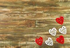 Coeurs floraux accrochant au-dessus du fond en bois de Brown Images stock