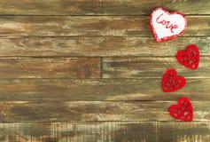 Coeurs floraux accrochant au-dessus du fond en bois de Brown Photographie stock libre de droits