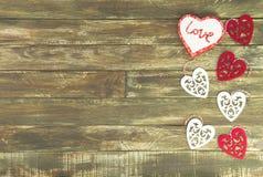 Coeurs floraux accrochant au-dessus du fond en bois de Brown de vintage Photographie stock