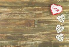 Coeurs floraux accrochant au-dessus du fond en bois de Brown de vintage Image libre de droits