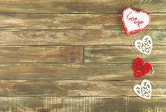 Coeurs floraux accrochant au-dessus du fond en bois de Brown de vintage Image stock