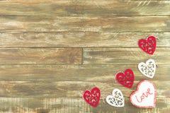Coeurs floraux accrochant au-dessus du fond en bois de Brown de vintage Photos stock