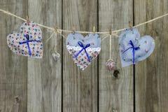 Coeurs floraux de tissu et serrures en forme de coeur accrochant sur la corde à linge par la barrière en bois rustique Photo stock