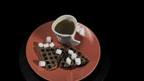 Coeurs foncés de gaufre d'un plat rouge avec la tasse de café sur le fond noir clips vidéos