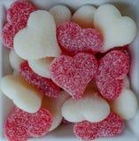 Coeurs gommeux rouges et blancs dans la cuvette sur le blanc photographie stock