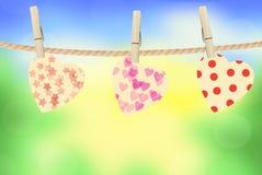 Coeurs lumineux accrochant sur la corde sur le fond lumineux de nature Images stock