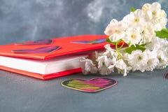 Coeurs noirs et roses sur un livre en couverture rouge et fleurs sur un fond concret gris Le concept de la Saint-Valentin Un symb Photographie stock libre de droits