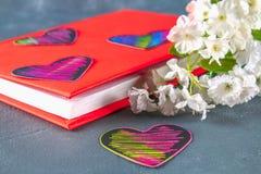 Coeurs noirs et roses sur un livre en couverture rouge et fleurs sur un fond concret gris Le concept de la Saint-Valentin Un symb Photo libre de droits