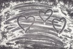 Coeurs peints avec le doigt dans le repas de blé sur une surface de fonctionnement grise Photo libre de droits