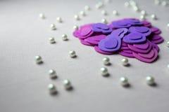 Coeurs pourpres et perles se trouvant sur un tissu beige Photos libres de droits