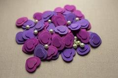 Coeurs pourpres et perles se trouvant sur un tissu beige Image libre de droits
