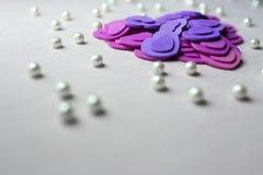 Coeurs pourpres et perles se trouvant sur un tissu beige Photographie stock libre de droits