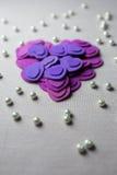 Coeurs pourpres et perles se trouvant sur un tissu beige Images stock