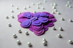 Coeurs pourpres et perles se trouvant sur un tissu beige Photo libre de droits