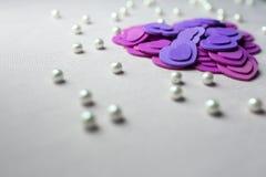 Coeurs pourpres et perles se trouvant sur un tissu beige Images libres de droits