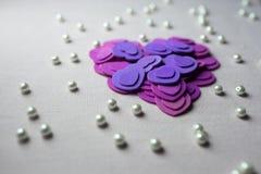 Coeurs pourpres et perles se trouvant sur un tissu beige Photos stock