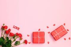 Coeurs, rose et boîte-cadeau rouges sur le fond rose photos stock