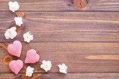 Coeurs roses de tricotage et fleurs blanches sur un fond en bois Images stock