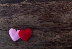 Coeurs roses et rouges placés sur le vieux plancher en bois Photos stock