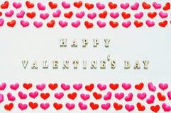 Coeurs roses rouges de textile et jour de valentines heureux d'inscription sur le fond en bois blanc Images stock