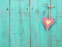 Coeurs rouges à carreaux et d'or remettant sur la porte en bois verte antique Images stock
