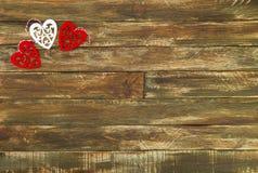 Coeurs rouges accrochant au-dessus du fond en bois de Brown Photographie stock