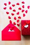 Coeurs rouges avec l'enveloppe et le boîte-cadeau sur le fond en bois Image libre de droits