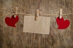Coeurs rouges avec la feuille de la pose de papier peint sur la corde à linge Photo libre de droits