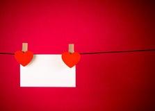 Coeurs rouges décoratifs avec la carte de voeux accrochant sur le fond rouge, concept de Saint Valentin Images stock