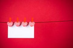 Coeurs rouges décoratifs avec la carte de voeux accrochant sur le fond rouge, concept de Saint Valentin Images libres de droits