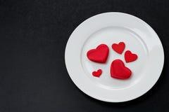 Coeurs rouges d'un plat blanc, un élément de fête de portion Photographie stock libre de droits