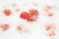Coeurs rouges dans la neige blanche Images stock