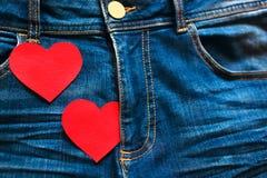 Coeurs rouges de carton sur des blues-jean dans un secteur intime Photos libres de droits